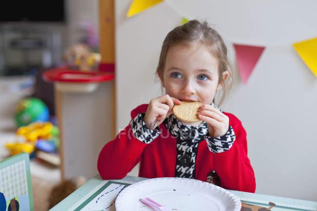 Маленькая девочка сидит за столом и ест печенье — стоковое фото