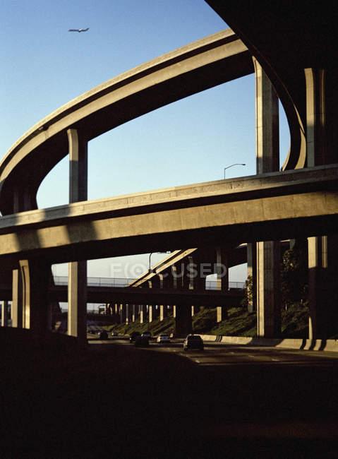 Vista distante de avião voando sobre o viaduto de rodovia de tráfego — Fotografia de Stock