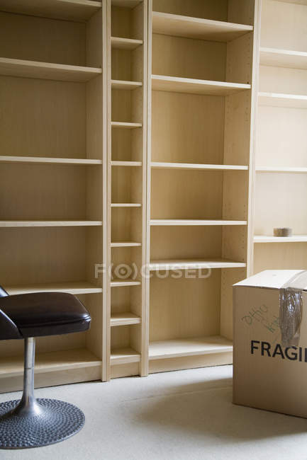 Chair and cardboard box in front of empty bookshelves — Stock Photo