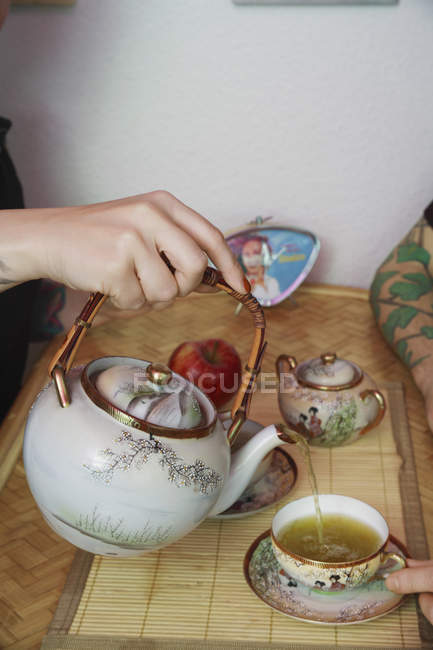A hand pouring green tea into cup — Stock Photo