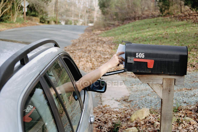 Person greift nach Briefen im Briefkasten — Stockfoto