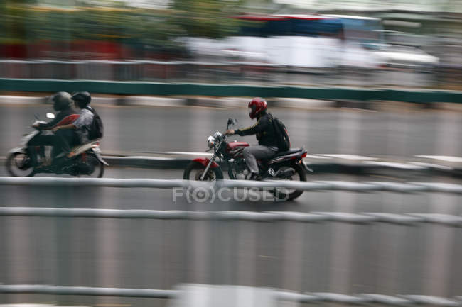 Side view of motorcycle rides on street scene — Stock Photo