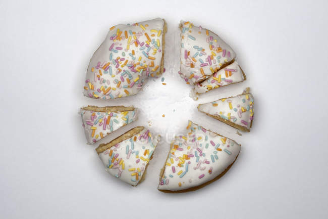 Directly above view of  doughnut cut into pieces on white background — Stock Photo
