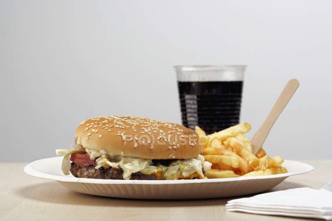 Hamburger et frites français sur papier plaque prochain verre de cola sur la table — Photo de stock