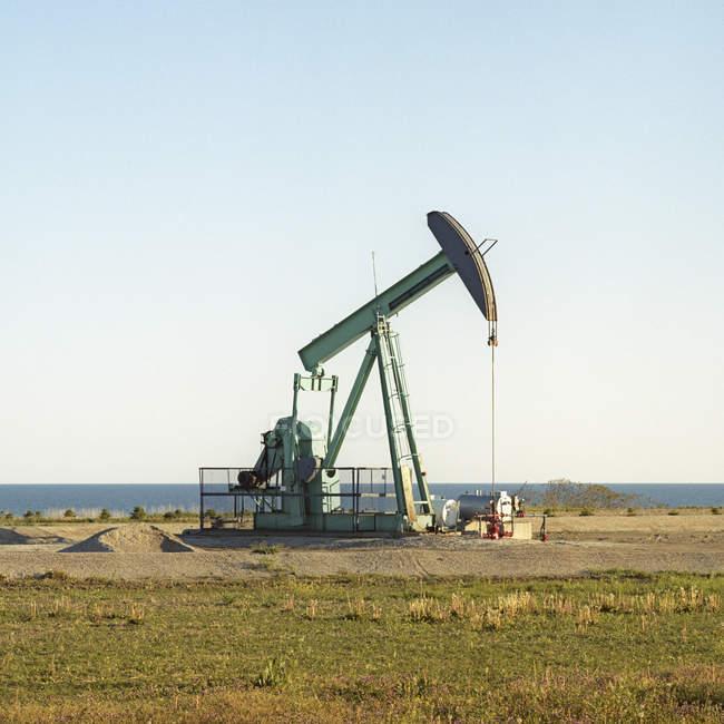 Pump jack pumping oil next to lake — Stock Photo