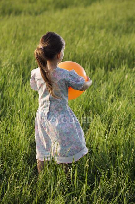 Задній вид дівчина, що проведення помаранчеві кулі в трав'янистих області — стокове фото