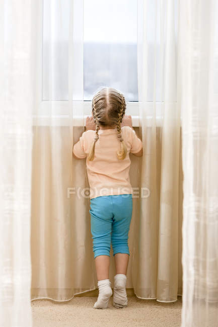 Little girl on her tiptoes trying to see out window — Stock Photo
