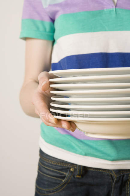Midsection of woman holding stack of white plates — Stock Photo