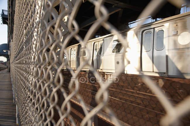 Поезд виден через проволочный забор, который отделяет пешеходную дорожку на Манхэттенском мосту — стоковое фото
