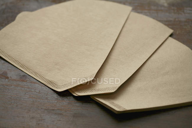 Beige paper coffee filters on wooden table — Stock Photo