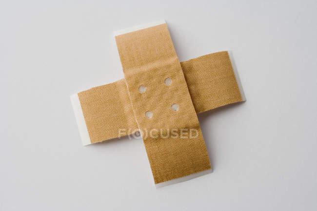 Deux pansements adhésifs en forme de croix — Photo de stock