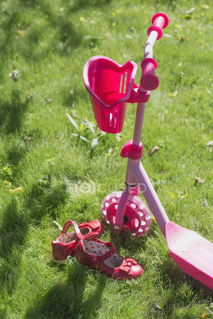 Pink push scooter and pink shoes on grass — Stock Photo