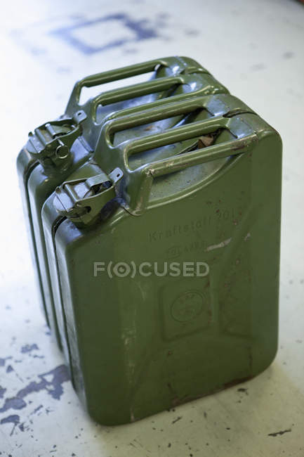 Old jerrican containers on floor — Stock Photo