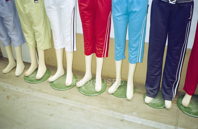 Low section of mannequins in row wearing tracksuit shorts — Stock Photo