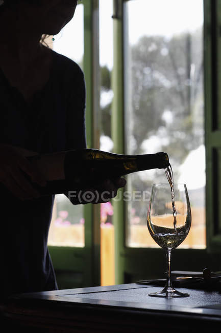 Silhouetted person pouring white wine into glass — Stock Photo