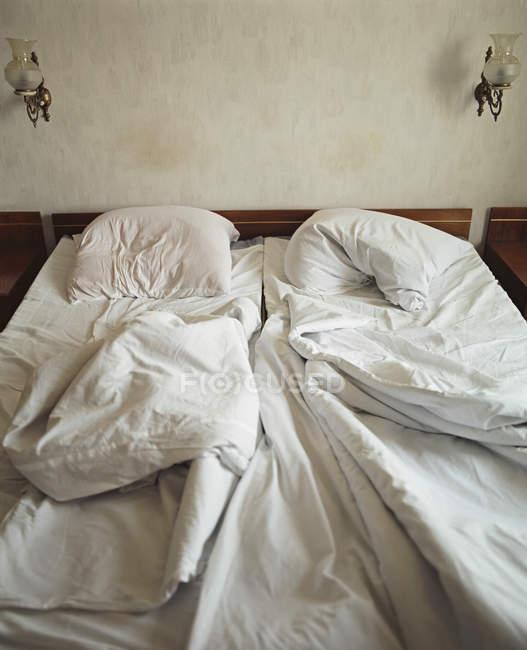 Vista para cama desfeita no quarto de hotel — Fotografia de Stock