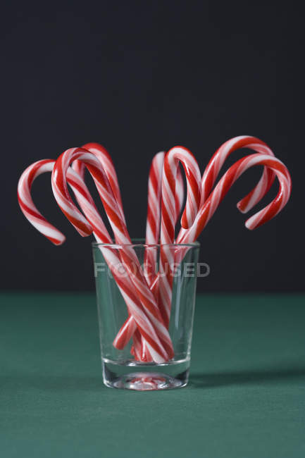 Candy canes in glass on dark background — Stock Photo
