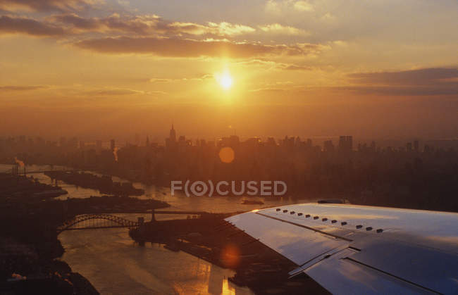 Sunset over city seen through airplane window — Stock Photo