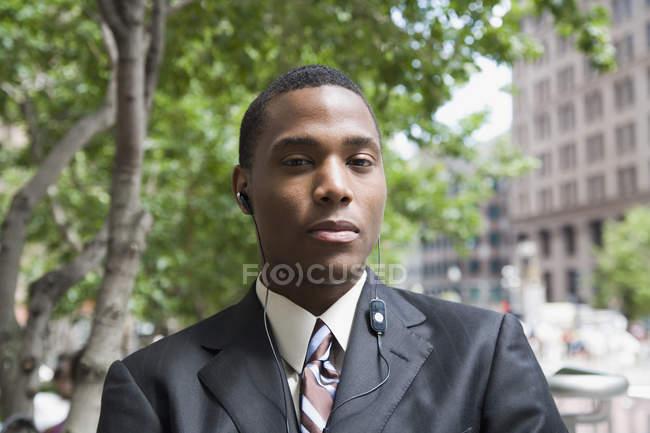 Бізнесмен, стоячи у фінансовому районі, слухаючи навушники — стокове фото
