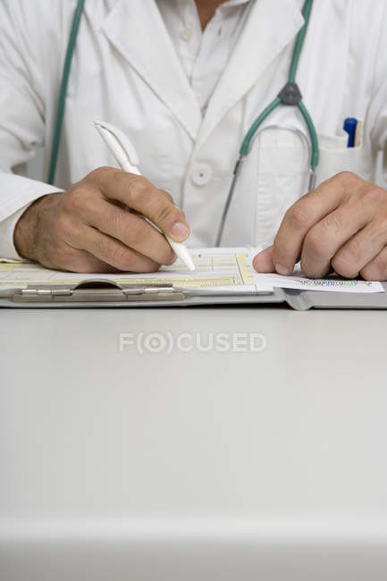 Close up view of doctor's hands writing at desk — Stock Photo