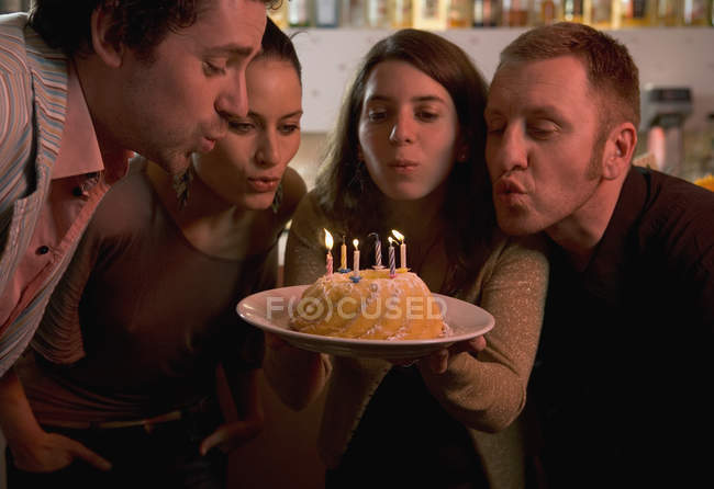 Group of friends blowing out candles on birthday cake — Stock Photo
