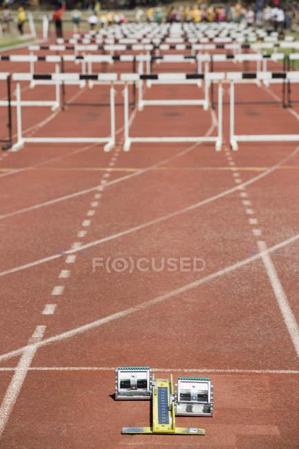 Obstacles disposés sur une piste de course derrière les blocs de départ — Photo de stock