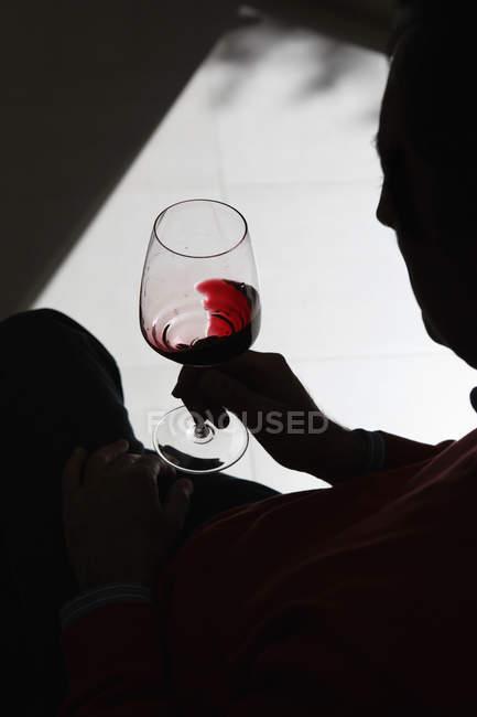 Silhouette Person wirbelnden Wein in Weinglas — Stockfoto