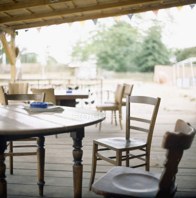 Vista para cadeiras vazias e mesas no pátio de madeira — Fotografia de Stock