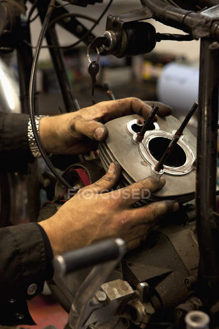 Mechanic's hands attaching cylinder to motorcycle's engine — Stock Photo