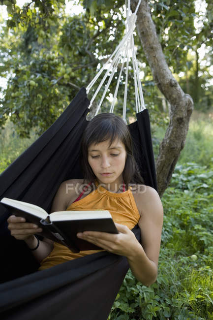 Young woman lying in hammock and reading — Stock Photo