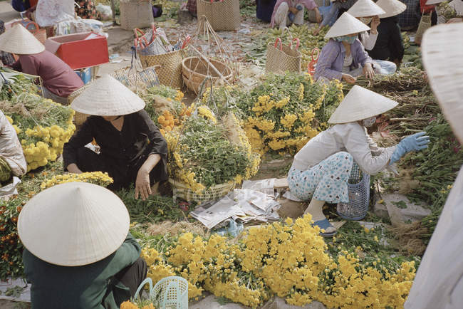 Group of women preparing flowers for market stall — Stock Photo