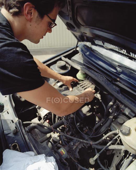 Jeune homme vérifiant une batterie de voiture — Photo de stock