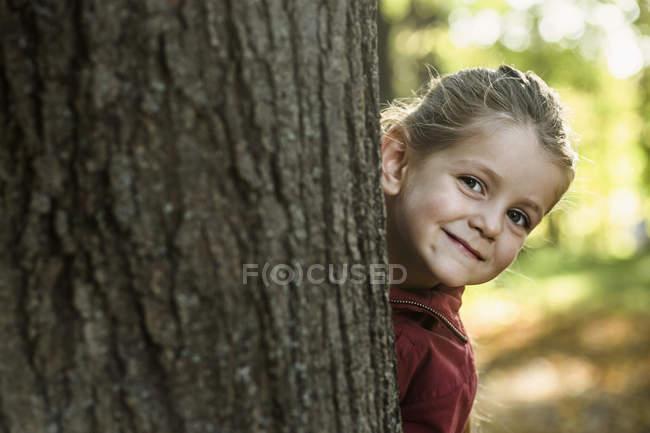 Uma jovem sorridente a espreitar por trás de um tronco de árvore — Fotografia de Stock