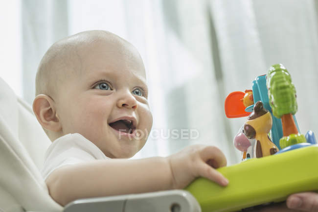 Baby in high chair with toy animals — Stock Photo