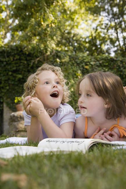 Zwei Mädchen liegen im Sommer nebeneinander im Hinterhof — Stockfoto