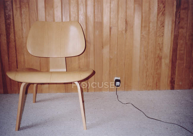 Retro chair next to outlet on wooden eall — Stock Photo