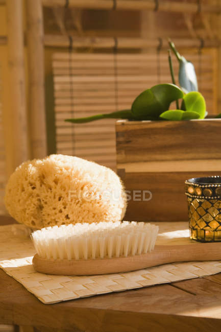 Still life of bath sponge with brush and candle on table — Stock Photo