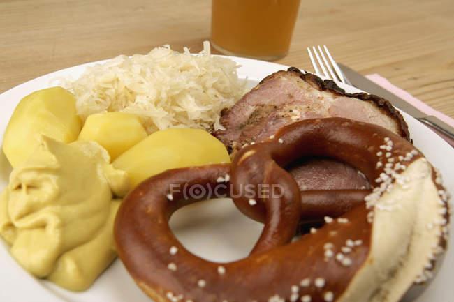 Plate of sauerkraut, potatoes and pretzel next to glass of beer — Stock Photo