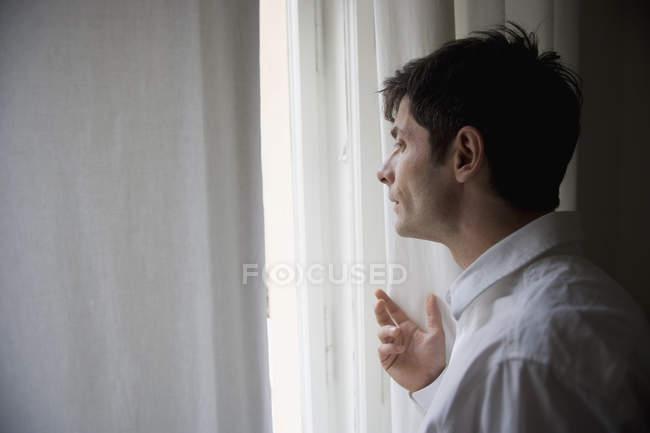 Закри вдумливий чоловік дивиться з вікна — стокове фото