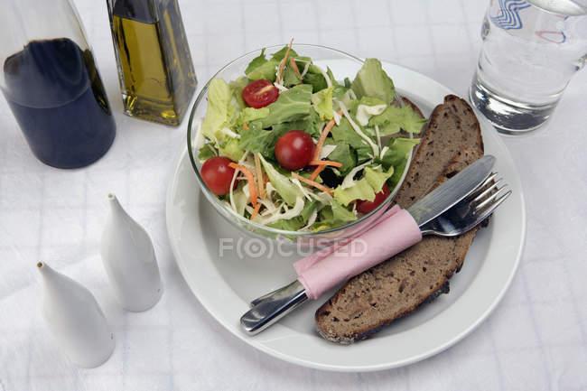 Salat und Brot auf Teller neben Olivenöl und Balsamico-Essig — Stockfoto