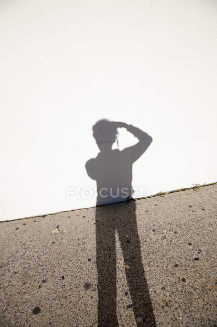 Photographer's shadow against ground and wall — Stock Photo
