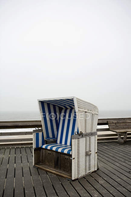 Hooded beach chair on boardwalk at foggy day — Stock Photo