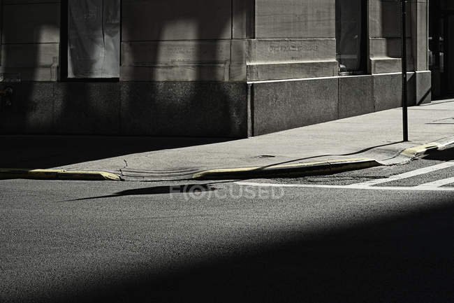 Shadowed road, pavement and building corner — Stock Photo