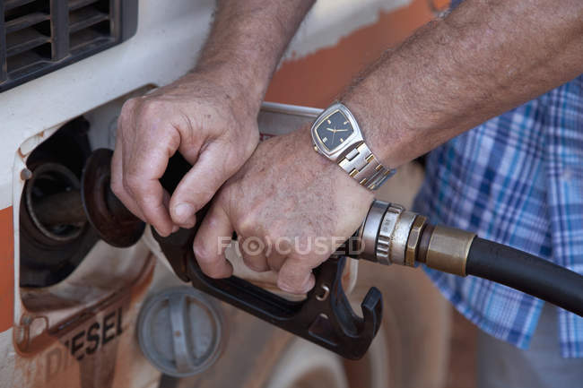 Crop male hands with watch refueling car — Stock Photo
