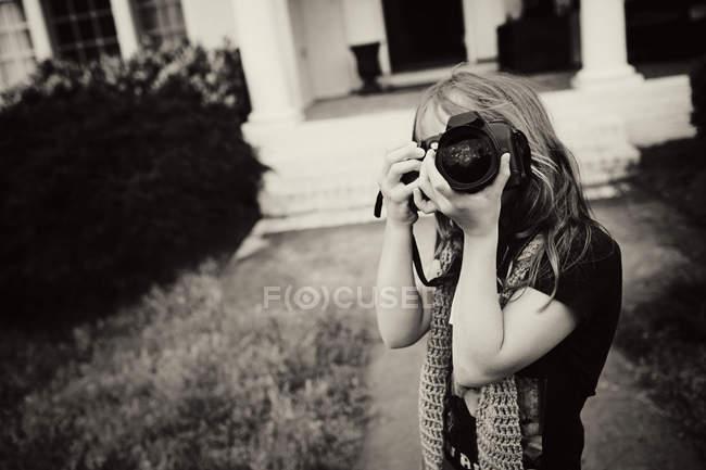 Retrato de jovem visando quintal com câmera — Fotografia de Stock