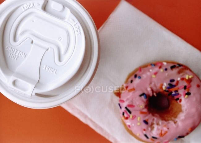 Directly above view of coffee cup and doughnut on napkin — Stock Photo