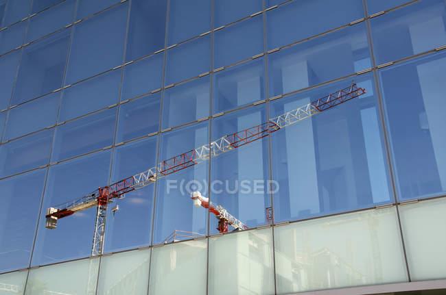 Отражение кранов на фасаде офисного здания — стоковое фото