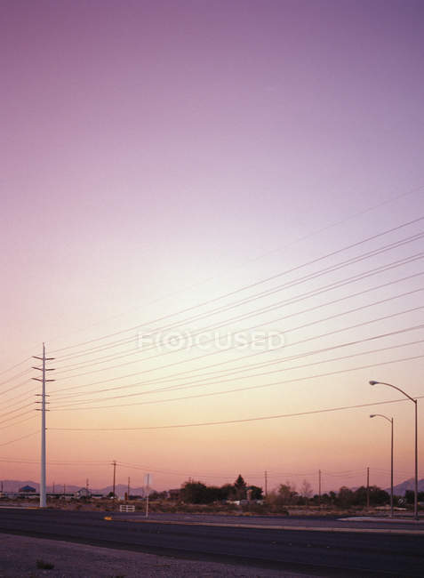 Power lines and street lights above pink sunset sky — Stock Photo