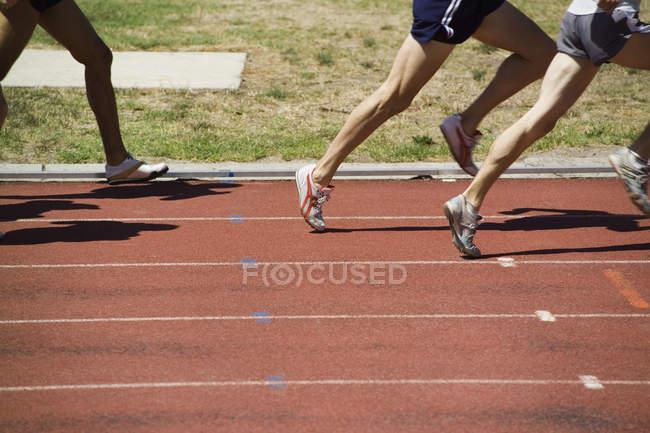 Низкая секция спортсменов мужского пола, бегающих по трассе — стоковое фото
