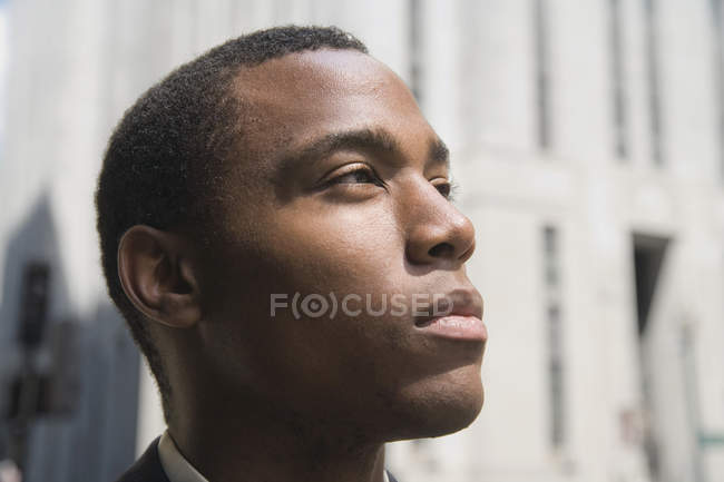 Young businessman in financial district looking up — Stock Photo